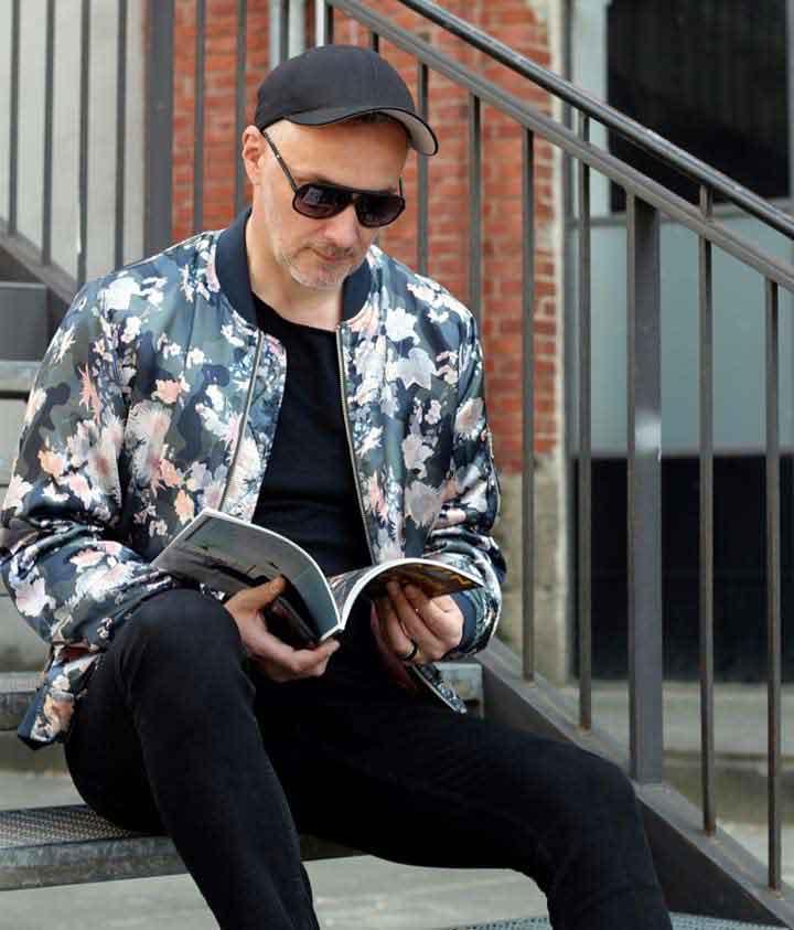 Mann mit stylischer Sommerjacke lesend auf Treppe auf dem Modeblog MoKoWo blog