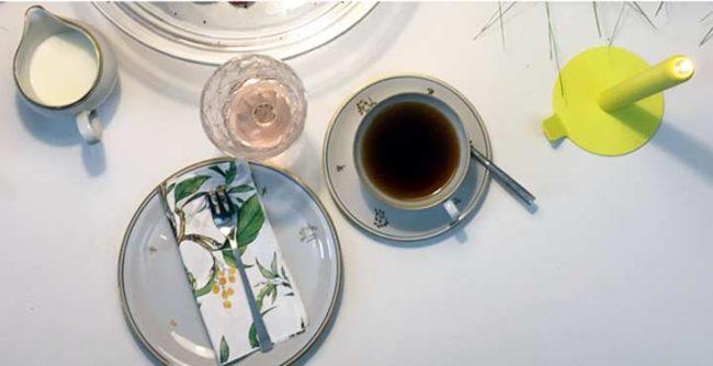 Draufsicht einer festlichen Tischdekoration mit Kaffee und Kuchen und Design Kerze von Lunedot