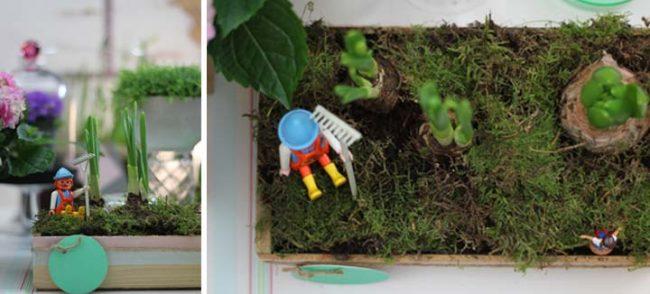 Bild Holzkiste mit Moos, Frühlingsblühern und Modellfigur von oben - Dekoration Interior Blog
