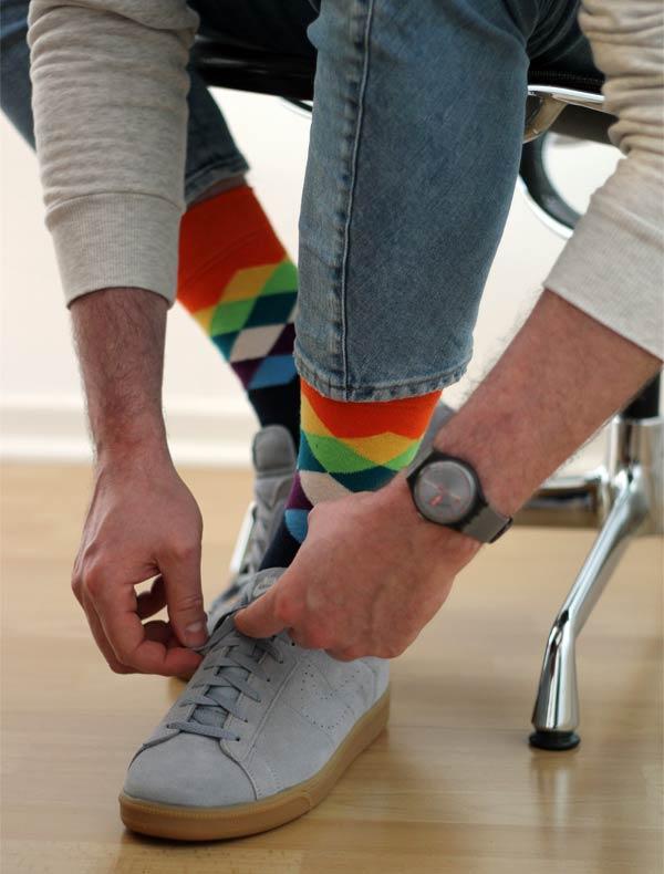 Happy Socks und graue Sneaker beim Schuhe zubinden auf dem Männer Modeblog